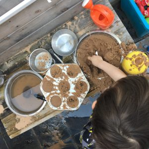 child playing with sand in a mud kitchen