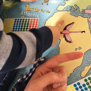 Children placing stickers on a map of the world