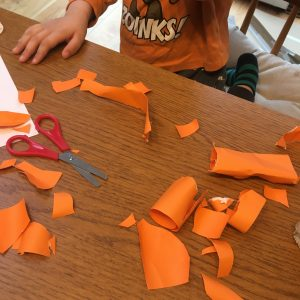 child's creation made from cut up orange paper